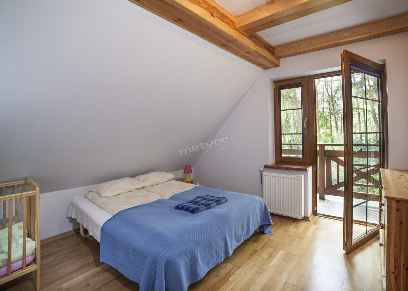dwuosobowa sypialnia małżeńska z łóżeczkiem niemowlęcym i balkonem