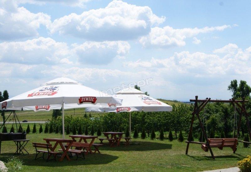 Ogródek z huśtawką, ławeczkami, parasolami oraz grillem i boiskiem do siatkówki.