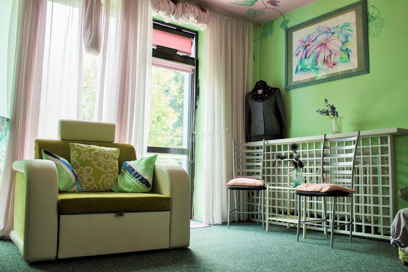 Słodkie Winogrona (5 osób) Sypialnia znajduje się na pierwszym piętrze. Bezpośrednio za drzwiami  sypialni mieści się duża łazienka z WC, prysznicem i wanną oraz dwoma umywalkami.  Łazienka dostępna jest dla trzech pokoi na tym piętrze. To kolorowe pomieszczenie upiększone jest malowidłami winogron na suficie i ścianach, ciekawymi obrazami oraz przeróżnymi fantazyjnymi dekoracjami. Na parapetach dorodne, żywe kwiaty. Ma się wrażenie siedzenia pod śródziemnomorskim baldachimem uwitym z gałęzi latorośli i winobluszczy. Aż by się chciało zerwać i smakować mięsistą kiść, która kusi swą krasą nad sypialnianymi legowiskami… W środku  jest pięć łóżek, w tym dwa podwójne. Pokój wyposażony jest w szafę, stoliki, krzesła, telewizor LCD, czajnik elektryczny i kubki. Dwa duże okna czynią wnętrze pełnym naturalnego światła. Sypialnia posiada też przestrzenny balkon ze stolikami i krzesłami wychodzący na zaciszny ogródek.  Wspólna przestrzeń socjalna znajduje się piętro niżej: w pełni w pełni wyposażona kuchnia (kuchnia ceramiczna, piekarnik elektryczny, kuchenka mikrofalowa, toster, dwa czajniki,  zmywarka do naczyń, dwa zlewozmywaki, zestaw garnków, naczyń, sztućców), piękna jadalnia, rozłożysty salon z kominkiem oraz taras z bezpośrednim wyjściem na ogród. Słodkie Winogrona to doskonałe miejsce na  beztroski  relaks!