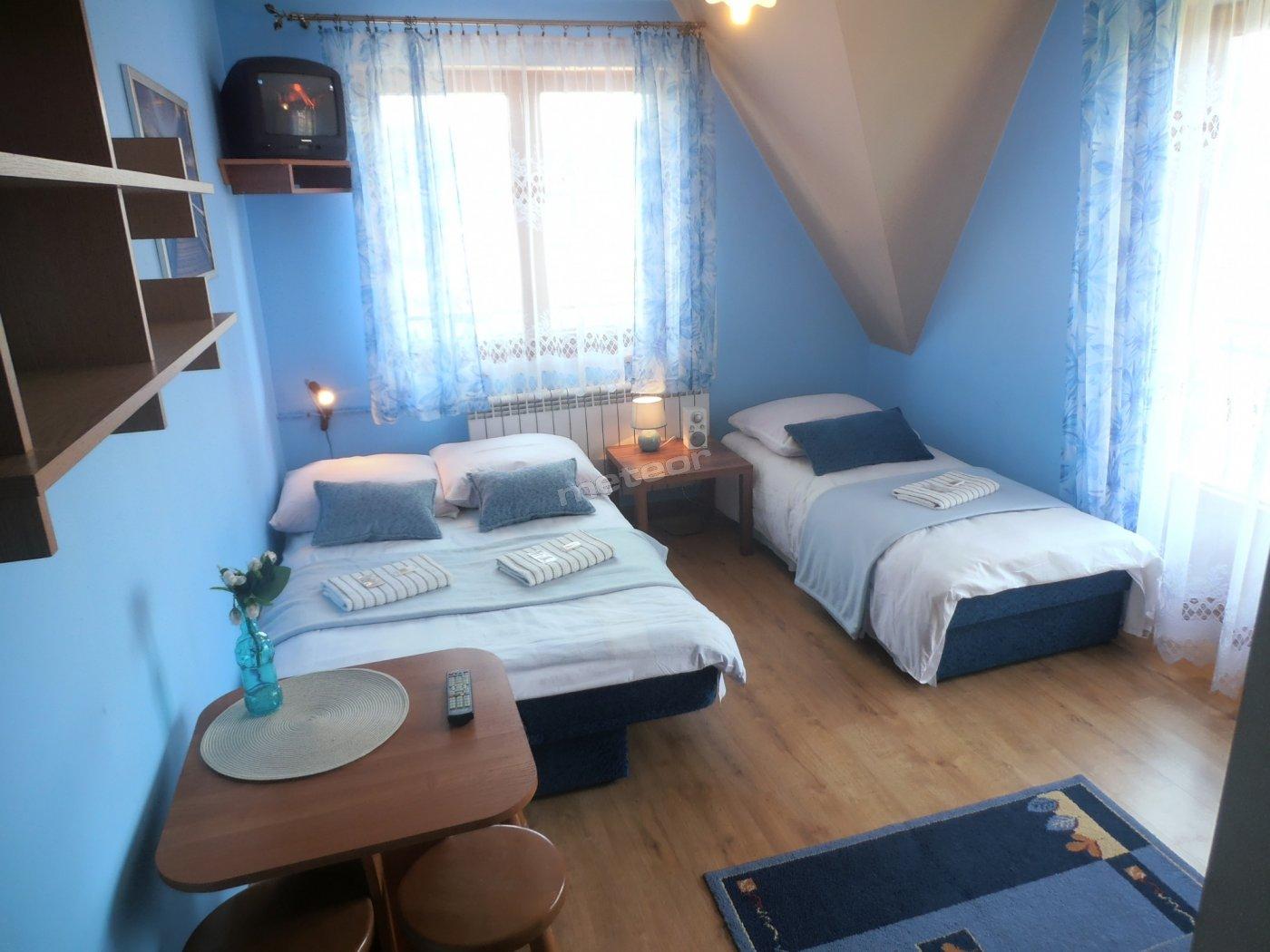 Niebieski - Przestronny, 3-os. pokój z balkonem i widokiem na panoramę Tatr, w błękitnych barwach. Wyposażony w TV, Wi-Fi i łazienkę; jedno łóżko małżeńskie, drugie 1. os. Możliwość dostawki.