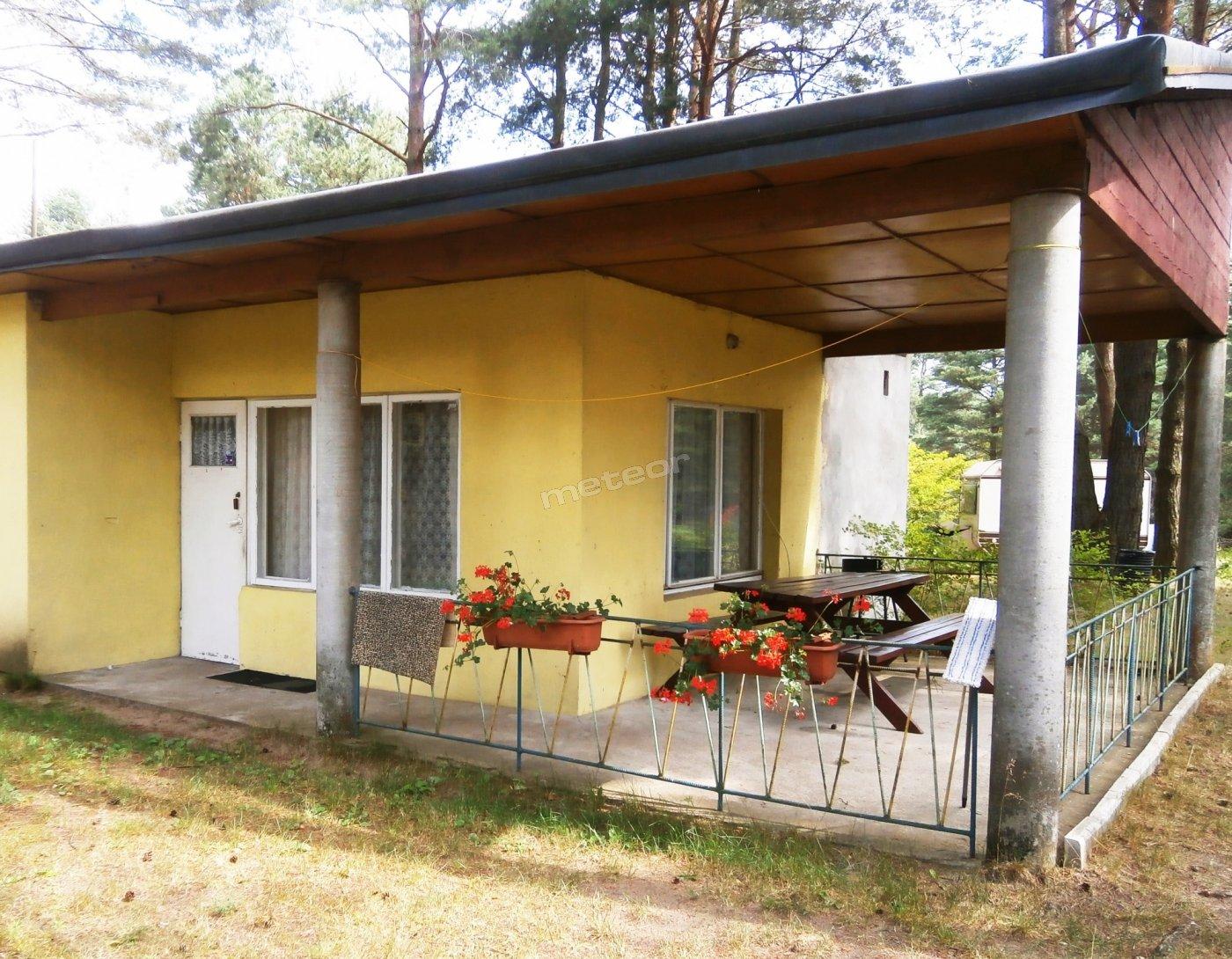 Domek z tarasem pokazany od zewnątrz.