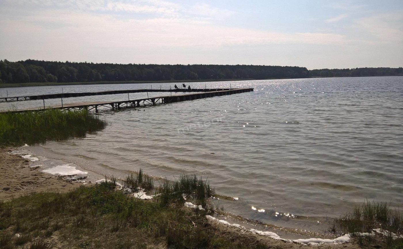 Jezioro Krasne z piaszczystą plażą, czystą wodą i pomostami dla wędkarzy.
