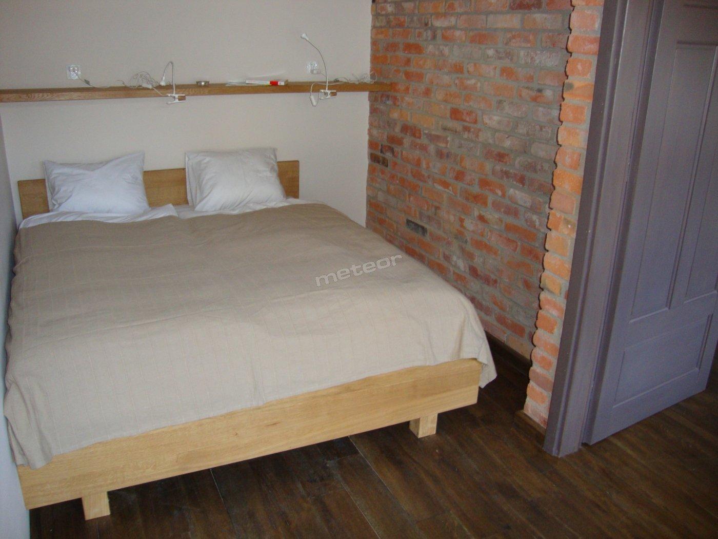 Wygodna sypialnia z łóżkiem małżeńskim w jednym z apartamentów.