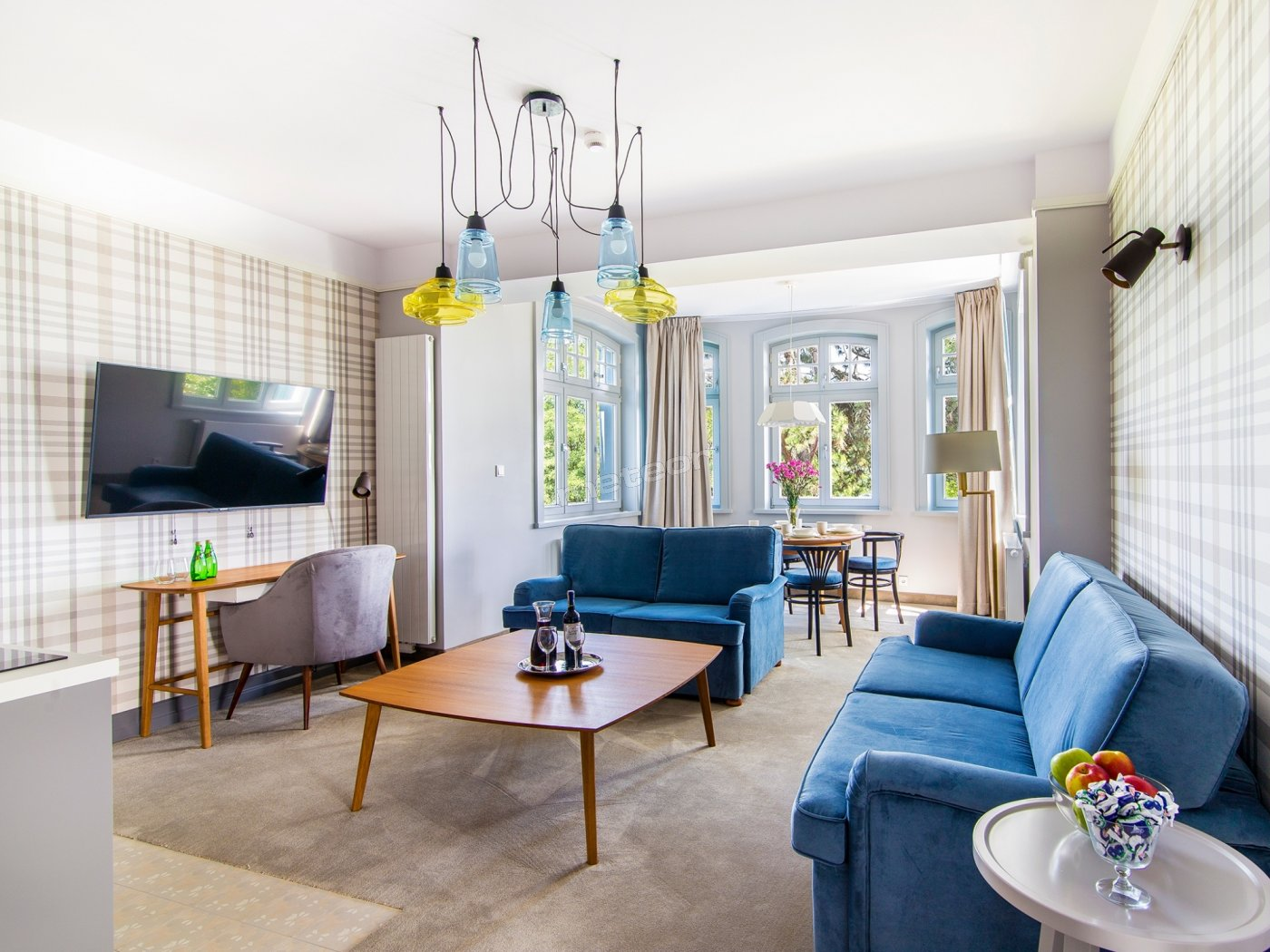 Pokój dzienny z rozkładaną sofą, aneksem kuchennym, jadalnią i częścią wypoczynkową.