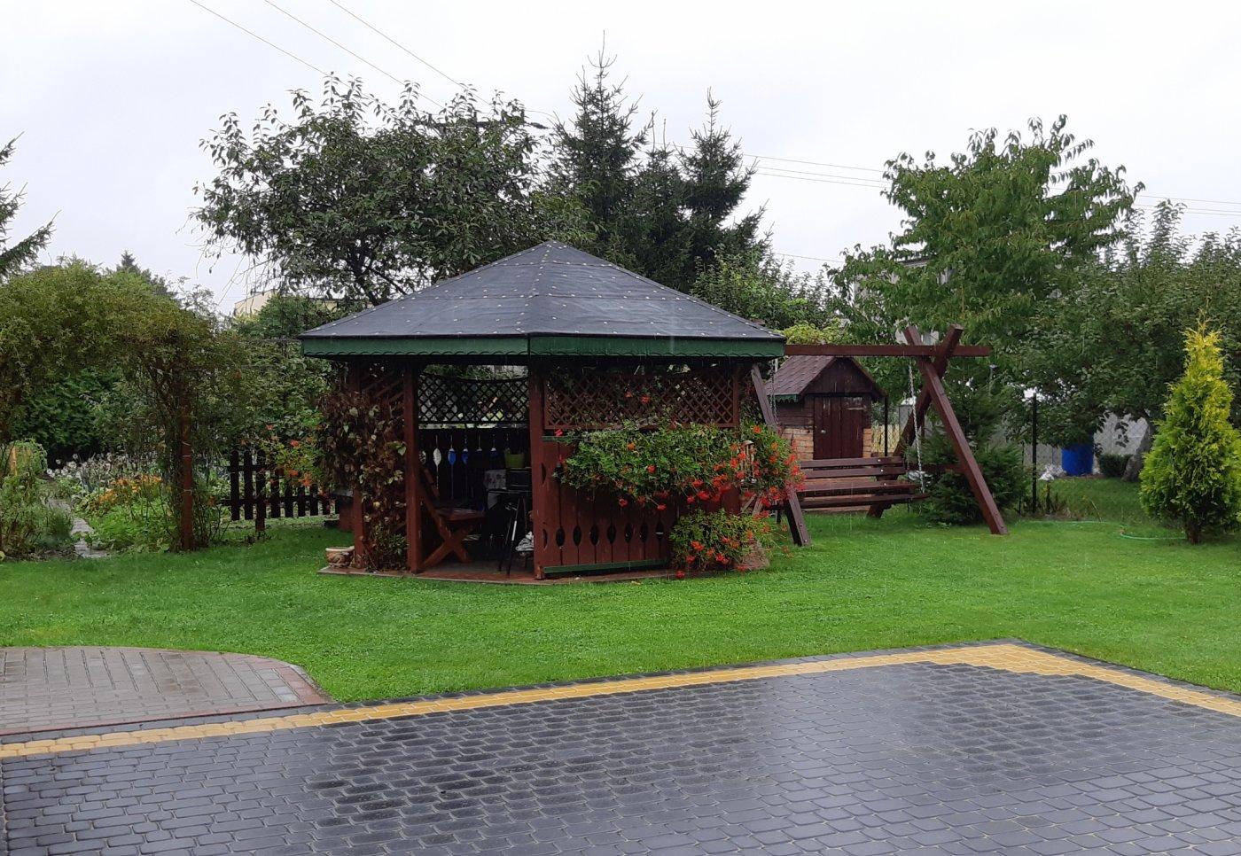 Przy domu:  altana, huśtawka, widoczna część ogrodu. Posesja  utwardzona kostka brukową.